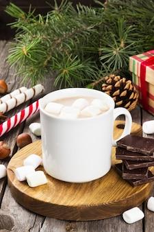 Xícara de chocolate quente com marshmallows em uma superfície escura