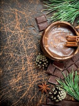 Xícara de chocolate quente com paus de canela na mesa rústica.