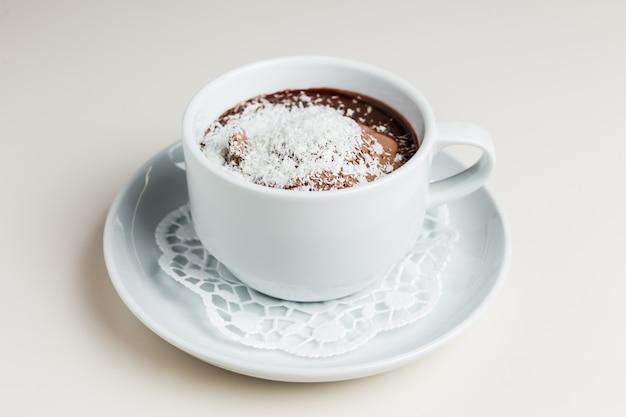 Xícara de chocolate quente com sorvete de chocolate e flocos de coco
