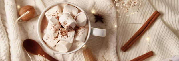 Xícara de chocolate quente com um marshmallow e decorações de natal. conceito de casa aconchegante de inverno