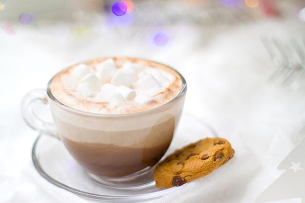 Xícara de chocolate quente de cacau com marshmallow e biscoitos de gengibre luzes desfocadas