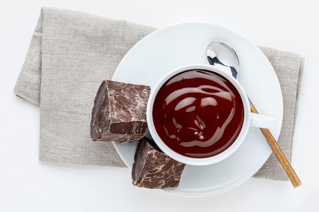 Xícara de chocolate quente delicioso e espesso para beber com barras de chocolate preto puro
