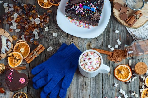 Xícara de chocolate quente e biscoitos entre bolo