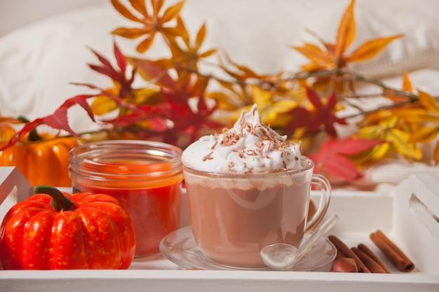 Xícara de chocolate quente e cremoso com espuma, abóboras e folhas secas