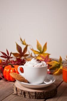 Xícara de chocolate quente e cremoso com espuma com folhas de outono e abóboras
