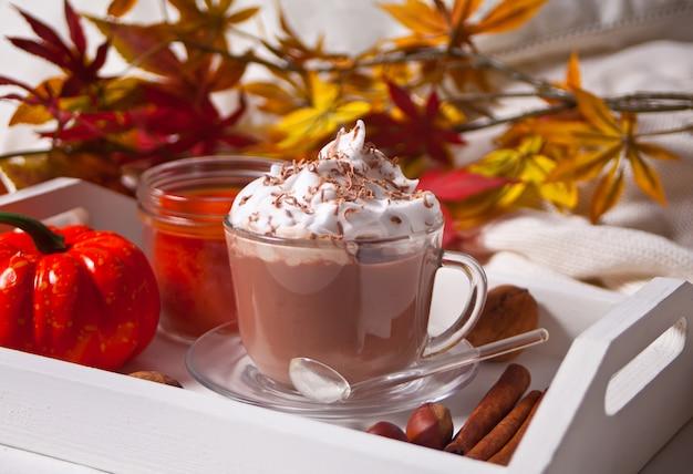 Xícara de chocolate quente e cremoso com espuma na bandeja branca com folhas de outono e abóboras