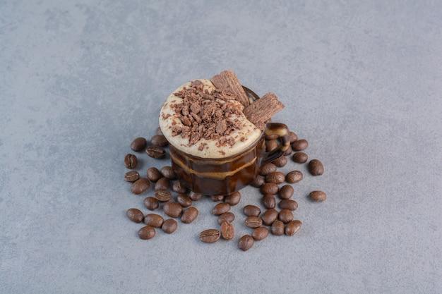 Xícara de chocolate quente e grãos de café em fundo de pedra.