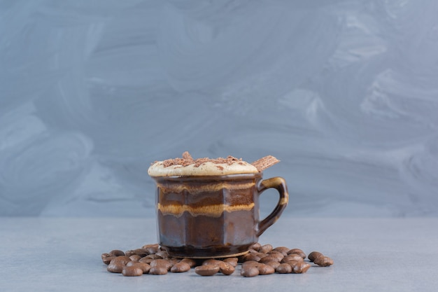 Xícara de chocolate quente e grãos de café na mesa de pedra.