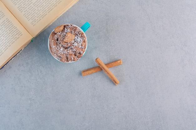 Xícara de chocolate quente e livro aberto sobre pedra.