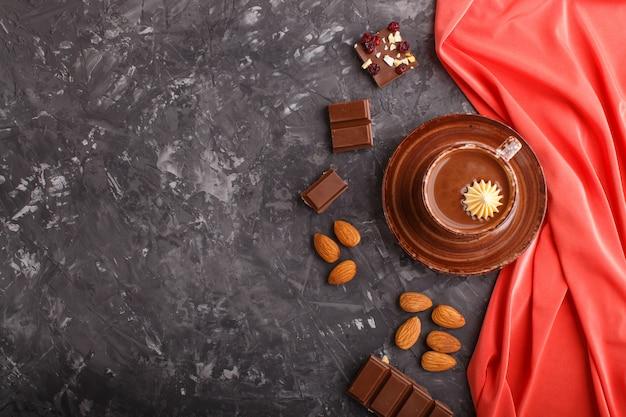 Xícara de chocolate quente e pedaços de chocolate ao leite com amêndoas em um fundo preto e concreto com têxtil vermelho.