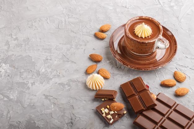 Xícara de chocolate quente e pedaços de chocolate ao leite com amêndoas