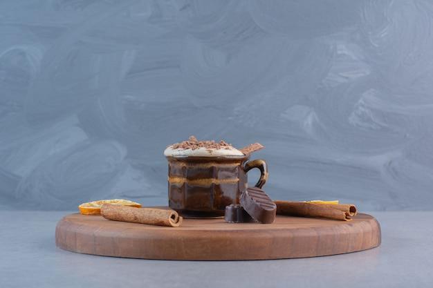 Xícara de chocolate quente e saborosos petiscos na placa de madeira.