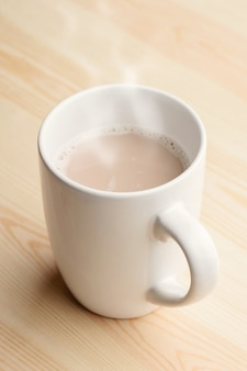 Xícara de chocolate quente fica na mesa de madeira