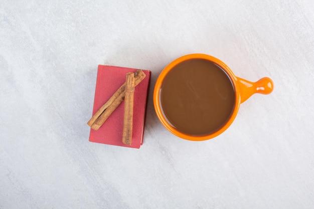 Xícara de chocolate quente, livro e canelas na superfície cinza