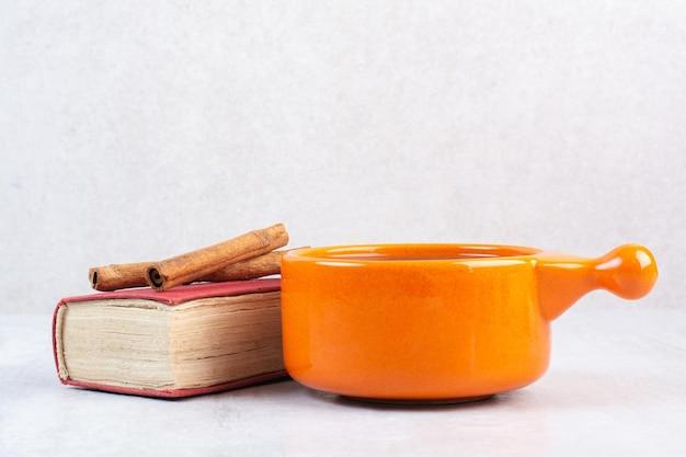 Xícara de chocolate quente, livro e canelas sobre fundo cinza. foto de alta qualidade
