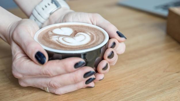 Xícara de chocolate quente nas mãos da mulher