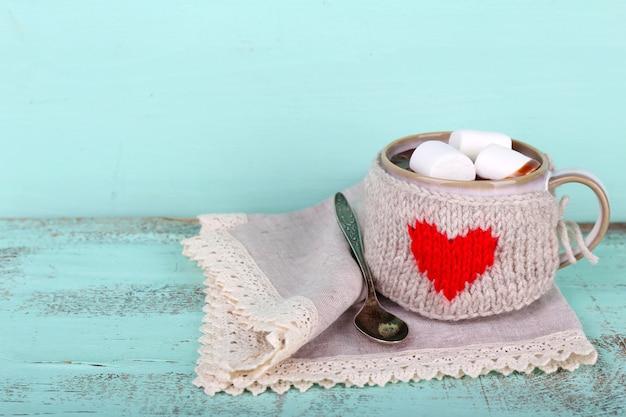 Xícara de chocolate quente saboroso, na mesa de madeira, na cor de fundo