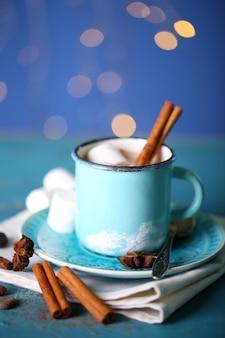 Xícara de chocolate quente saboroso, na mesa de madeira, no fundo brilhante