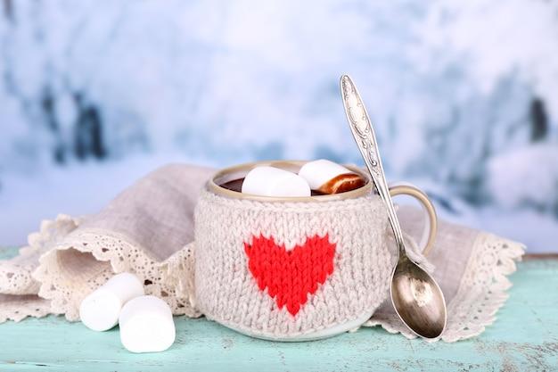 Xícara de chocolate quente saboroso, na mesa de madeira, sobre fundo claro