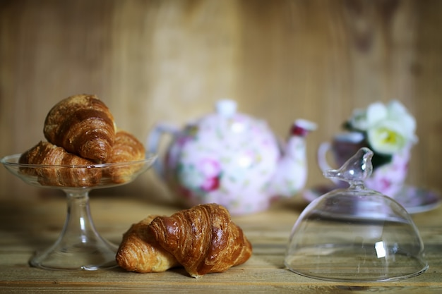 Xícara de croissant café da manhã com fundo de madeira