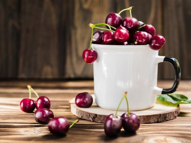Xícara de doce de cereja fresca no fundo de madeira