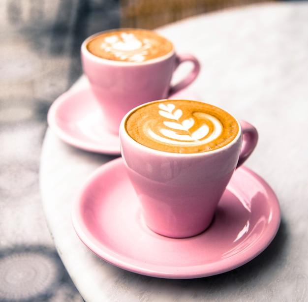 Xícara de duas xícaras de café com leite quente no fundo da mesa de mármore
