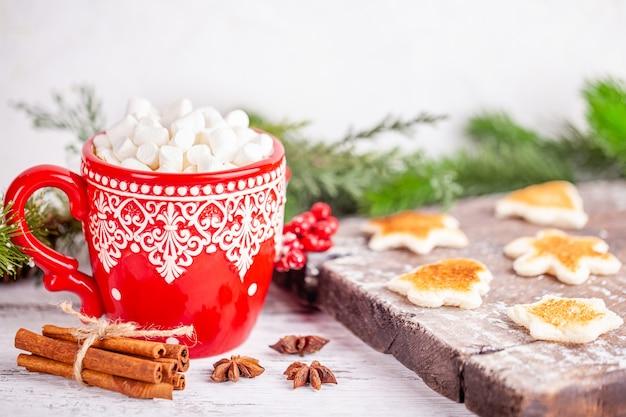 Xícara de estação fria com chocolate quente e marshmallows na decoração de inverno