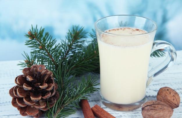 Xícara de gemada com ramos de pinheiro na mesa