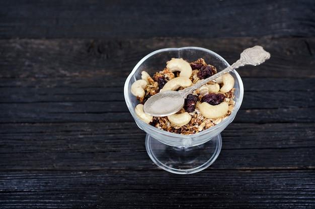 Xícara de granola com cajus em uma mesa de madeira preta. vista do topo. pequeno-almoço americano tradicional