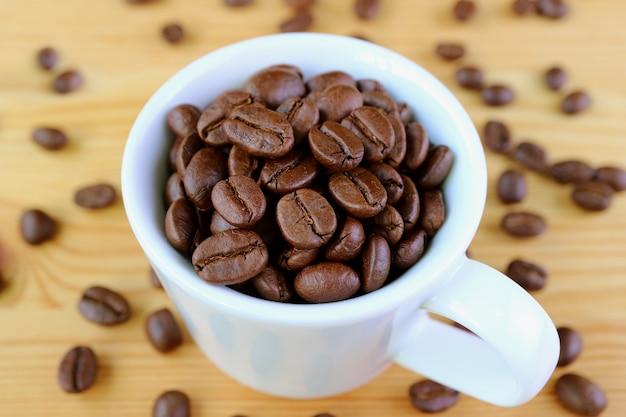 Xícara de grãos de café torrados na madeira