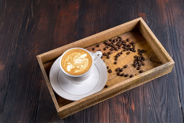 Xícara de latte art em xícara com grãos de café em uma bandeja de madeira