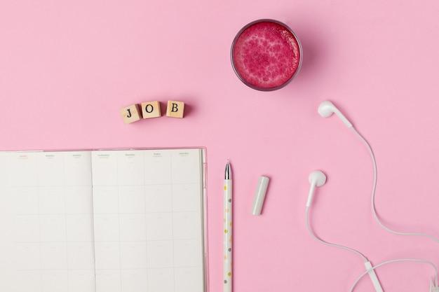 Xícara de latte de beterraba rosa superalimento na moda, caneta, bloco de notas
