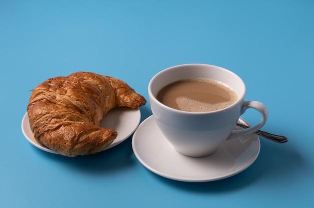 Xícara de leite, café e croissant sobre fundo azul, copie o espaço para texto.