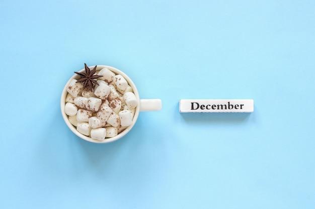 Xícara de marshmallows de cacau e calendário de dezembro em fundo azul