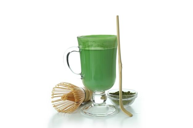 Xícara de matcha com leite e acessórios para fazer isolado no fundo branco