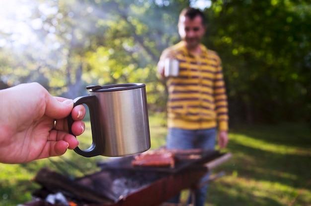 Xícara de metal de piquenique na mão de uma mulher torcendo com amigo masculino na fumaça de churrasco