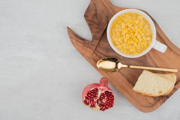 Xícara de milho doce com fatia de pão na placa de madeira