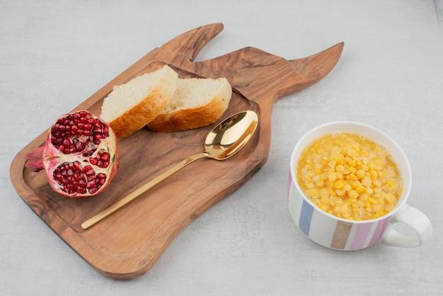 Xícara de milho doce na superfície de madeira com fatia de pão e romã