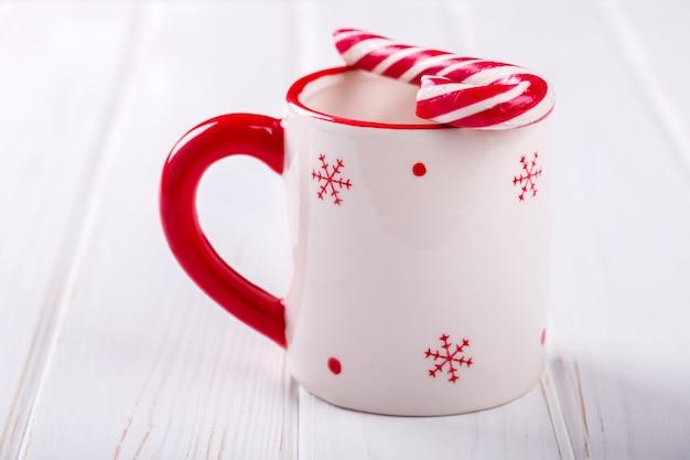 Xícara de natal branco com doce vermelho
