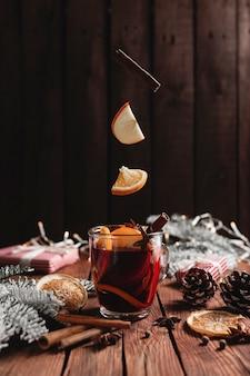 Xícara de natal com quentão na mesa levitando laranja em pau de canela