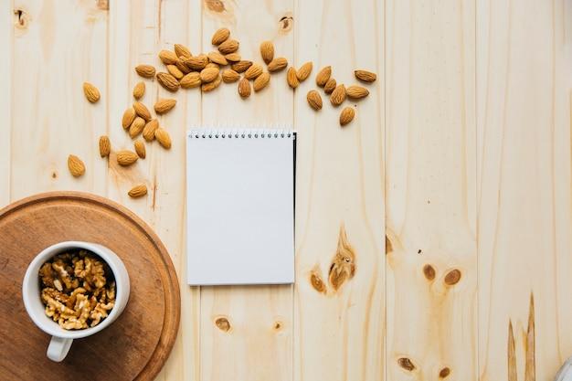 Xícara de nozes perto do bloco de notas em branco e amêndoas em pano de fundo de madeira