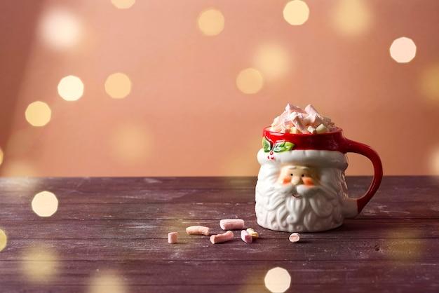 Xícara de papai noel de natal de chocolate quente com marshmallow na mesa de madeira. conceito de comida e bebida de natal