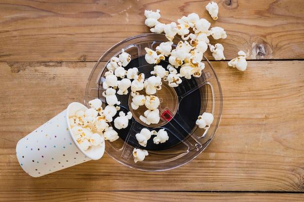 Xícara de pipoca em cima da fita do cinema