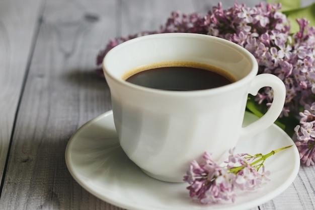 Xícara de porcelana com café e lilás