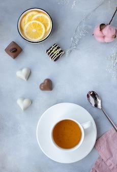 Xícara de porcelana de chá de ervas, rodelas de limão e doces variados sobre uma superfície cinza com flores. tempo de primavera. imagem vertical, vista superior, plana