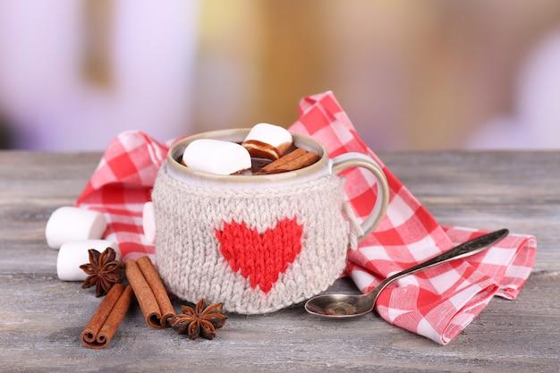 Xícara de saboroso chocolate quente, na mesa de madeira,