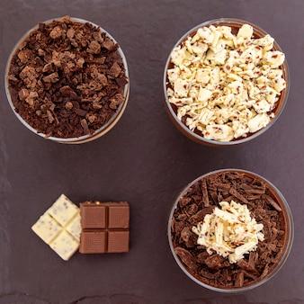 Xícara de sobremesa com mousse de chocolate ao leite e raspas de chocolate branco e mousse de ganache.
