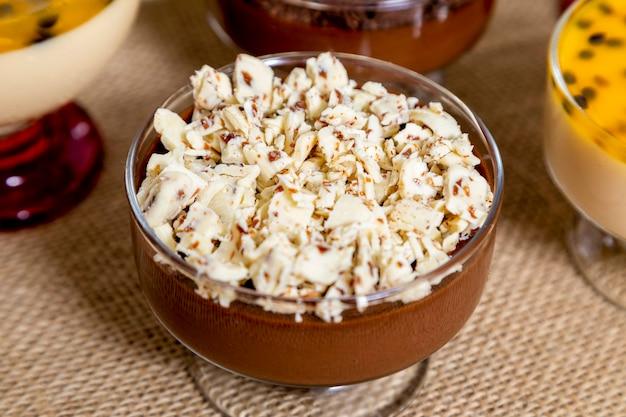 Xícara de sobremesa com mousse de chocolate ao leite e raspas de chocolate branco, mousse de ganache e mousse de maracujá.