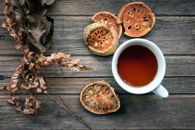 Xícara de suco de bael seco em fundo de madeira com frutas secas bael