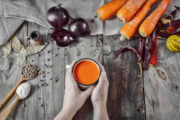 Xícara de suco de cenoura nas mãos femininas em uma superfície de madeira cinza